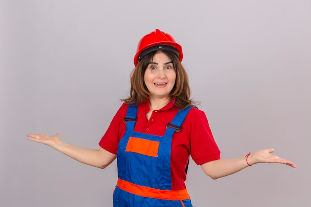 Builder woman in construction uniform and safety helmet looking surprised shrugging shoulders spreading hands not understanding what happened clueless and confused expression over isolated white b