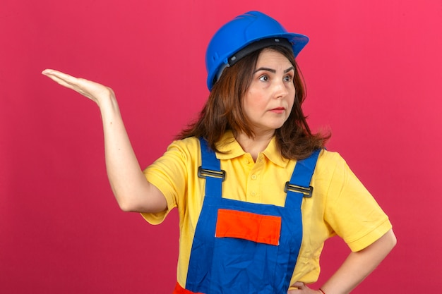 Builder woman in construction uniform and safety helmet shrugging shoulders raising hand not understanding what happened clueless and confused expression over isolated pink wall