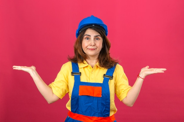 Builder woman in construction uniform and safety helmet shrugging shoulders spreading hands not understanding what happened clueless and confused expression over isolated pink wall
