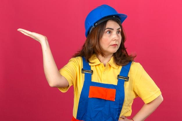 Женщина-строитель в строительной форме и защитном шлеме пожимает плечами, поднимает руку, не понимая, что произошло, невежественное и смущенное выражение лица над изолированной розовой стеной