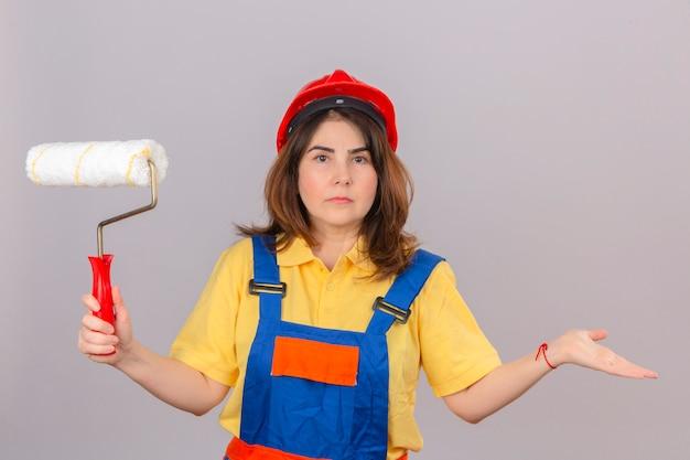 Женщина-строитель в строительной форме и защитном шлеме стоит с малярным валиком в руке, пожимая плечами, разводя руками, не понимая, что произошло, невежественное и смущенное выражение лица