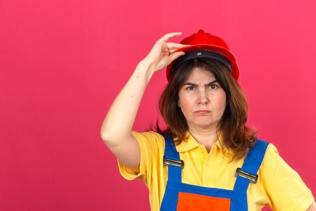 Женщина-строитель в строительной форме и защитном шлеме с нахмуренным лицом трогает шлем рукой, стоящей над изолированной розовой стеной