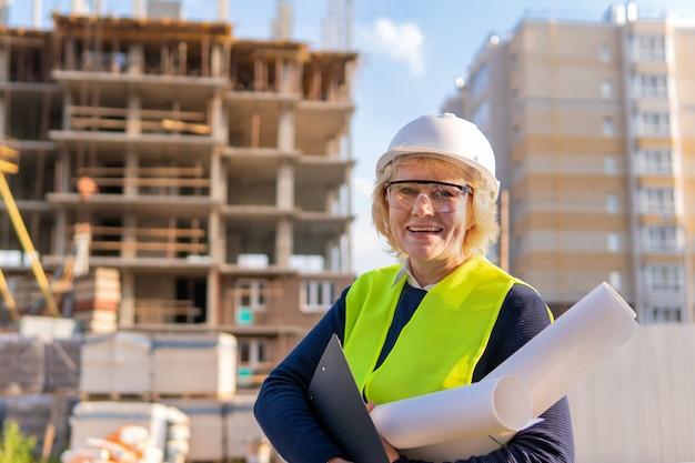 Женщина построителя на строительной площадке в зеленом жилете и белом шлеме с чертежной бумагой и таблеткой. женщина средних лет в очках смотрит в камеру. она улыбается.