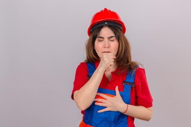 Женщина-строитель в строительной форме и защитном шлеме чувствует себя плохо и кашляет, стоя над изолированной белой стеной