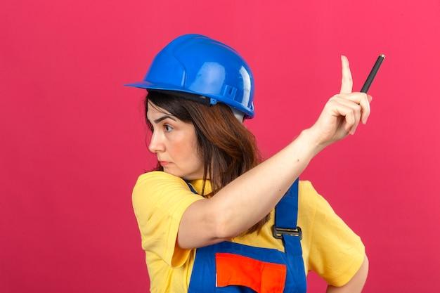 Женщина-строитель в строительной форме и защитном шлеме смотрит в сторону, указывая пальцем вверх, предупреждая над изолированной розовой стеной