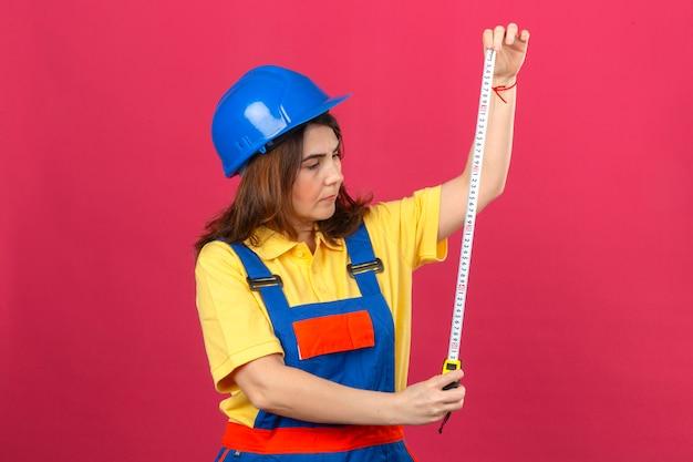 고립 된 분홍색 벽 위에 심각한 얼굴로 손에 측정 테이프를보고 건설 유니폼과 안전 헬멧을 착용 작성기 여자
