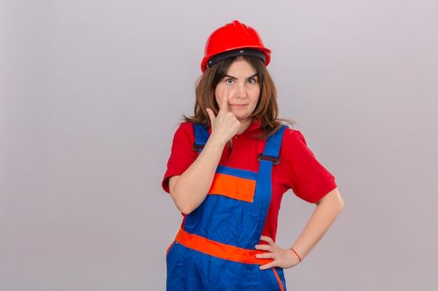 Женщина-строитель в строительной форме и защитном шлеме, указывая в глаза, наблюдая, как вы жестикулируете с подозрительным выражением лица, стоя над изолированной белой стеной