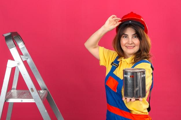 ペイントを伸ばして顔に笑顔で梯子の上に立って建設制服と安全ヘルメットを身に着けているビルダー女性は分離ピンクの表現上の手で彼女のヘルメットに触れることができます。