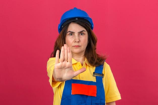 Женщина-строитель в строительной форме и защитном шлеме стоит с открытой рукой и делает знак остановки с серьезным и уверенным жестом защиты над изолированной розовой стеной
