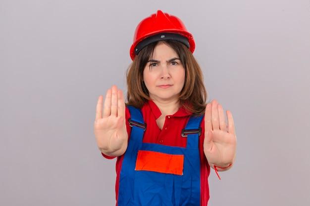 Женщина-строитель в строительной форме и защитном шлеме, стоящая с открытыми руками и делающая знак остановки с серьезным и уверенным выражением лица, защищая жест над изолированной белой стеной