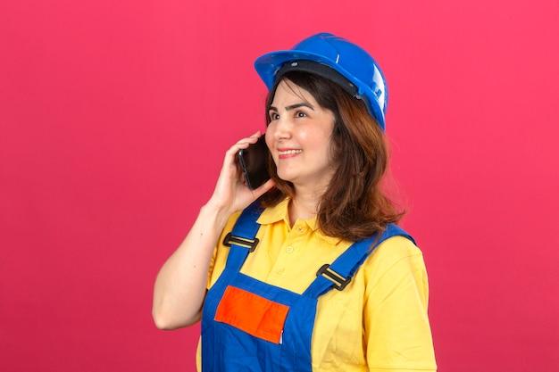Женщина-строитель в строительной форме и защитном шлеме разговаривает по мобильному телефону, весело улыбаясь над изолированной розовой стеной