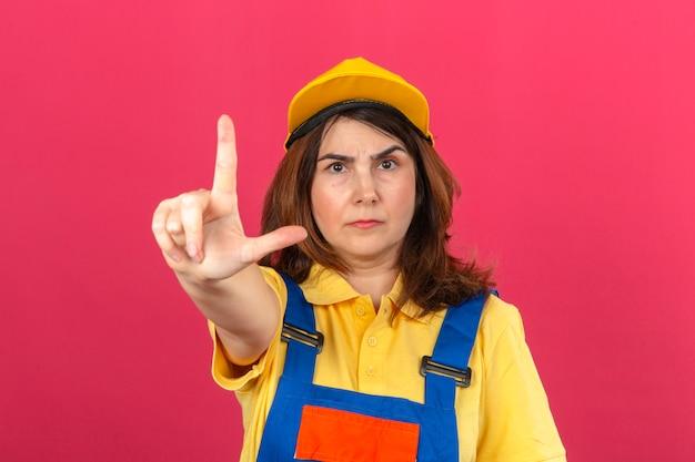 Женщина-строитель в строительной форме и желтой кепке, указывающая пальцем вверх, и сердитое выражение, не показывающее жестов над изолированной розовой стеной