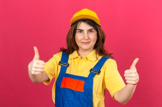 孤立したピンクの壁の上に立って親指を示すフレンドリーな笑みを浮かべて建設制服と黄色の帽子を着てビルダー女性