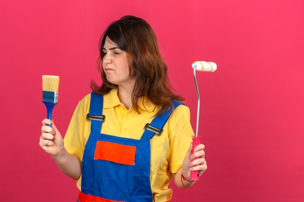 Builder woman wearing construction uniform holding paint roller and brush looking at it with sad expression displeased over isolated pink wall