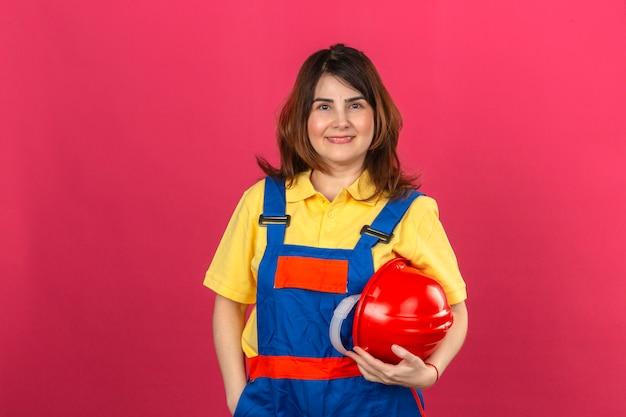 Casco di sicurezza d'uso della tenuta dell'uniforme della costruzione della donna del costruttore a disposizione con il sorriso sul fronte felice che controlla parete rosa isolata