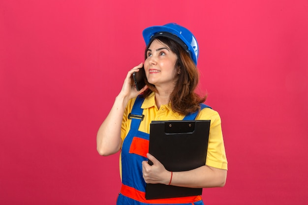 Builder woman wearing construction uniform and safety helmet holding clipboard while talking on mobile phone looking up with smile on face over isolated pink wall