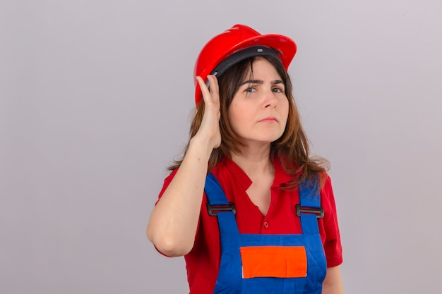 Builder woman wearing construction uniform and safety helmet holding hand near her ear trying to listen to the conversation of someone over isolated white wall