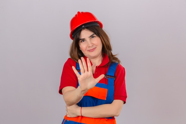 Builder woman wearing construction uniform and safety helmet holding her hand up telling do not come closer over isolated white wall