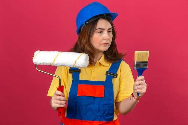 Builder woman wearing construction uniform and safety helmet holding paint roller and brush looking at them with serious face over isolated pink bavkground