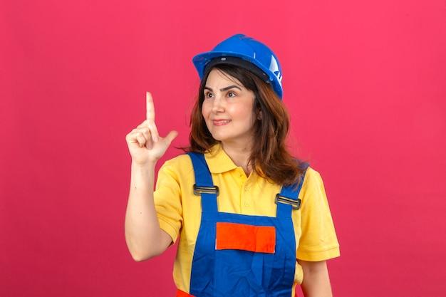 Uniforme della costruzione della donna del costruttore e casco di sicurezza che guardano da parte che indicano dito su che sorride avendo nuova idea che controlla parete rosa isolata