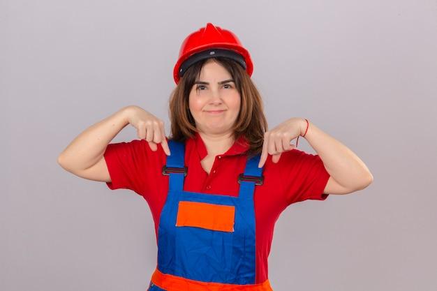 Uniforme della costruzione della donna del costruttore e casco di sicurezza che sembrano sicuri con il sorriso sul fronte che indica con i dito indice giù sopra la parete bianca isolata