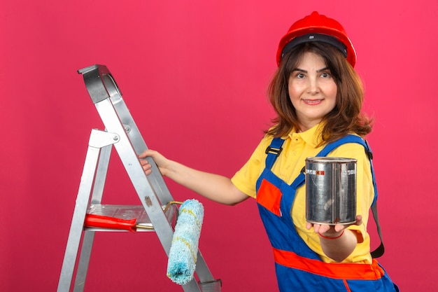 Builder woman wearing construction uniform and safety helmet standing on ladder with smile on face stretching out paint can over isolated pink wall
