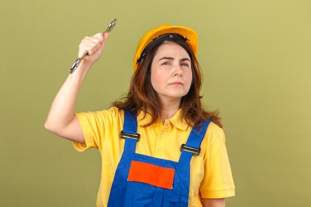 Uniforme della costruzione della donna del costruttore e casco di sicurezza che minacciano di colpire con la chiave che guarda con l'espressione sospettosa che controlla parete verde isolata
