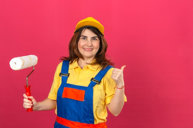 Builder woman wearing construction uniform and yellow cap holding paint roller and showing thumb up smiling cheerful over isolated pink wall