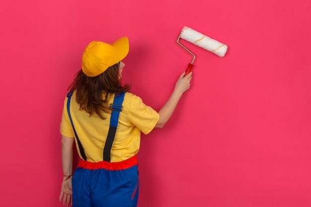 Uniforme della costruzione della donna del costruttore e cappuccio giallo che stanno con lei indietro con il rullo di pittura e che dipingono sopra la parete rosa isolata
