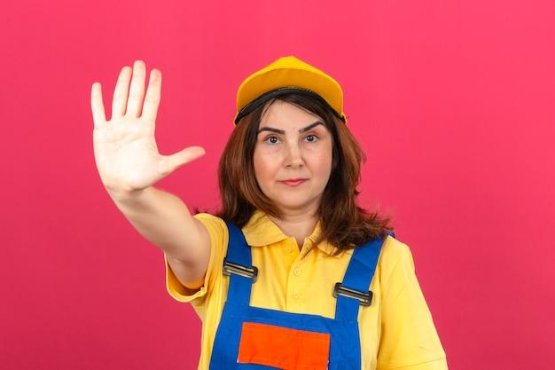 Uniforme d'uso e cappuccio giallo della costruzione della donna del costruttore che stanno con la mano aperta che fa il fanale di arresto con il gesto serio e sicuro della difesa di espressione sopra la parete rosa isolata