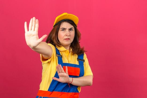 Uniforme d'uso e cappuccio giallo della costruzione della donna del costruttore che stanno con le mani aperte che fanno il fanale di arresto con il gesto serio e sicuro della difesa di espressione sopra la parete rosa isolata