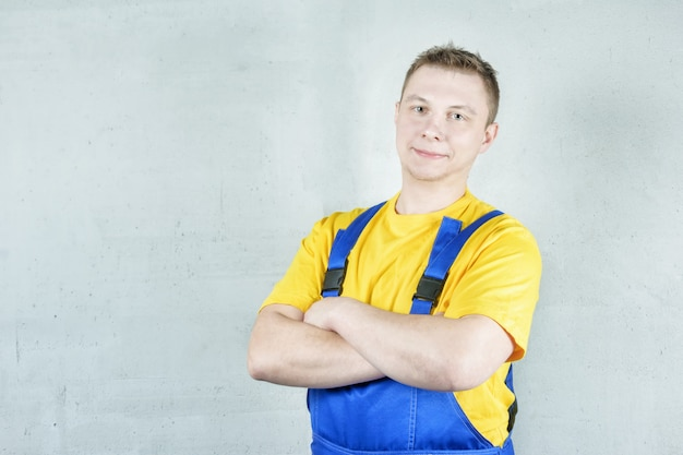 Builder in work clothes against a gray wall. the man folded his arms across his chest.