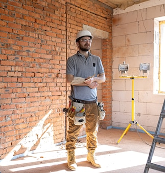 A builder in work clothes examines a construction drawing at a construction site