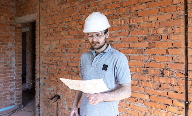 A builder in work clothes examines a construction drawing at a construction site.