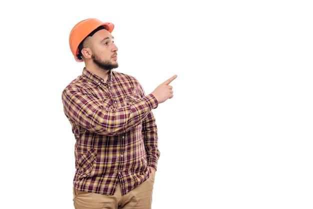 白い背景で隔離、右を指している保護構造のオレンジ色のヘルメットの手でビルダーの労働者。テキスト用のスペースをコピーします。働く時間。