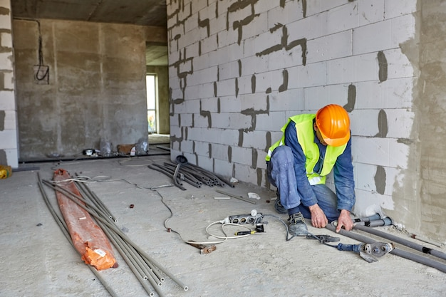 Builder in working clothes and orange safety hard hat is installing plastic pipes using modern tools in a flat of building under construction
