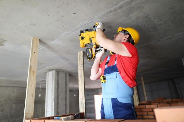 Строитель работает со спецтехникой на потолке.