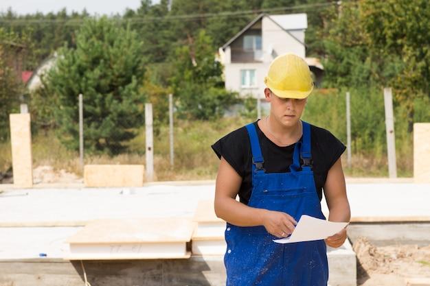 ビルダーは、ヘルメットとオーバーオールの現場に立っているときに、仕様や建築材料の順序を確認します
