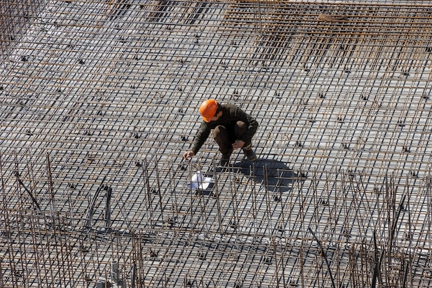 Builders in hard hats and protective vests work at the construction site of a multistorey building