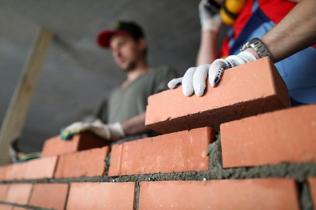 Строители производят стеновые кирпичи и цементные технологии