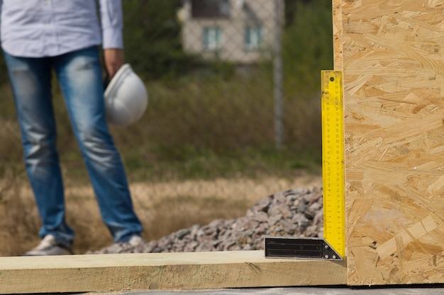 건축업자는 목재 벽 패널이 정확히 수직인지 확인하기 위해 건설 현장에서 정사각형 또는 직각을 사용하려고 시도합니다.