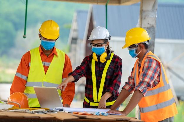 건축, 건설중인 주거 건물의 개념에 청사진 안전 헬멧을 착용하는 건축업자.
