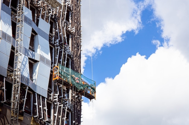 건축업자 노동자가 비즈니스 건물의 정면에 유리창을 설치합니다.