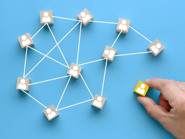 성공적인 팀 구축. 파란색 배경에 사람 아이콘이 있는 나무 큐브입니다. 팀 빌딩 개념입니다.