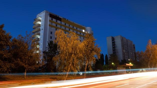 Здание и дорога с деревьями ночью