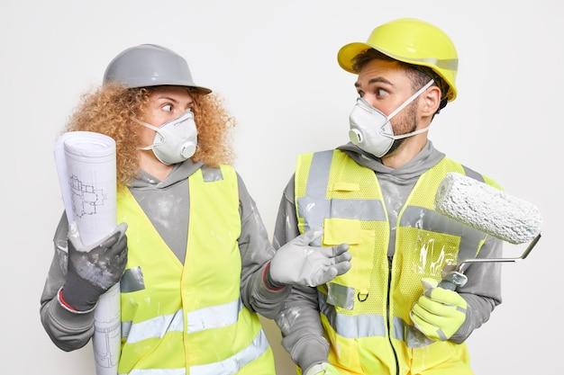 建物とチームワークのコンセプト。驚いた女性と男性のエンジニアや建築家は、安全服を着た家の改善と改修に取り組んでいるお互いにショックを受けているように見えます青写真を準備します
