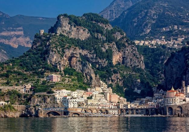 昼間の山と海岸の間の建物