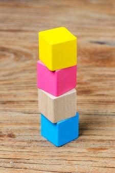 Blocchi di costruzione su sfondo di legno, blocchi di legno variopinti di legno