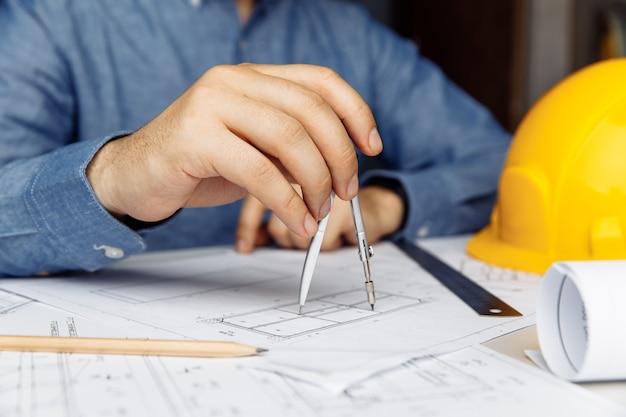 Строительная концепция гражданского мужчины-инженер, работающая над архитектурным проектом плана на столе в офисе
