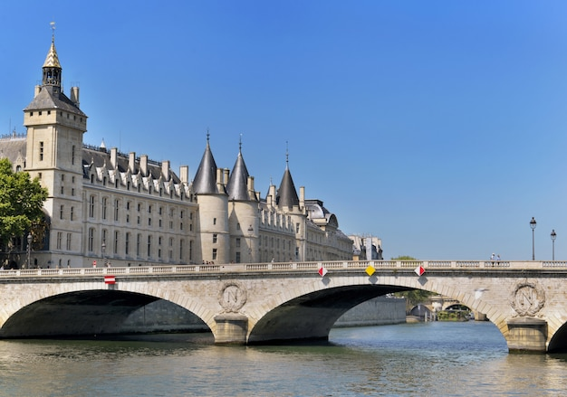 Building of the conciergerie in paris view from riverbank of the seine from bridge of invalides